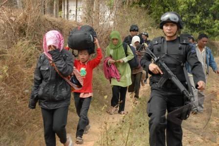 Escortés par la police, des villageois chiites de Sampang, à Madura, évacuent leur domicile après l'attaque dont ils ont été victimes, faisant un mort (Antara/Saiful Bahri).