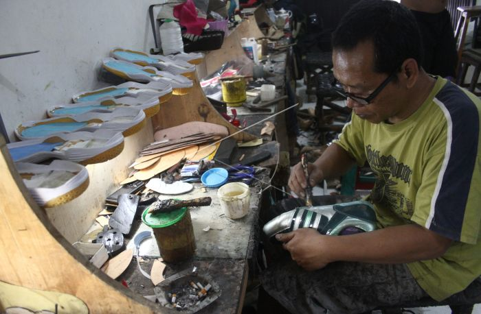 Seorang pekerja mengoleskan lem pada sepatu yang dibuatnya sebelum dijual  dengan harga Rp. 100.000 hingga 500.000 rupiah per pasang di pabrik sepatu  di ... d0c7de4ef1